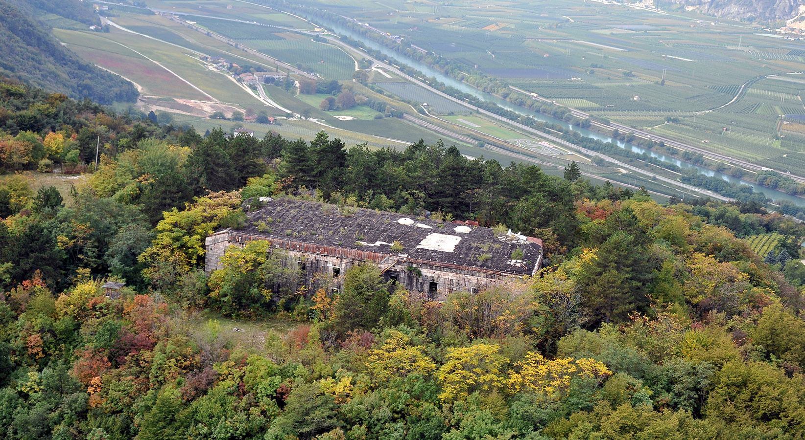 Una delle strutture del Forte di Mattarello e, sullo sfondo, l'abitato di Aldeno (www.trentinograndeguerra.it)
